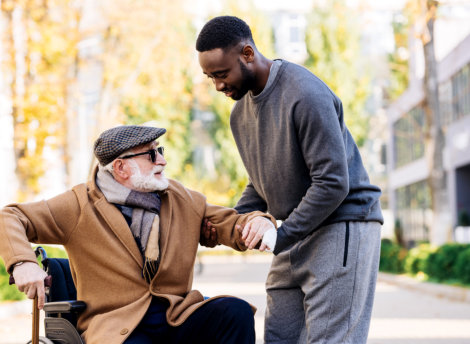 caregiver helping senior man get off from his wheelchair