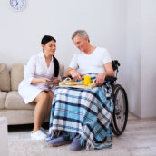senior man eating his meal with his caregiver on his side