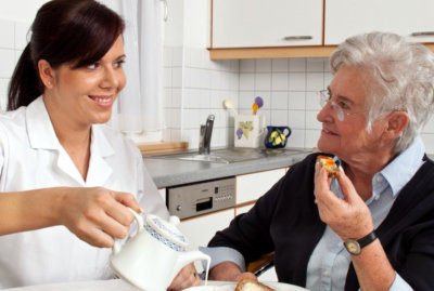 caregiver and senior woman eating their meal